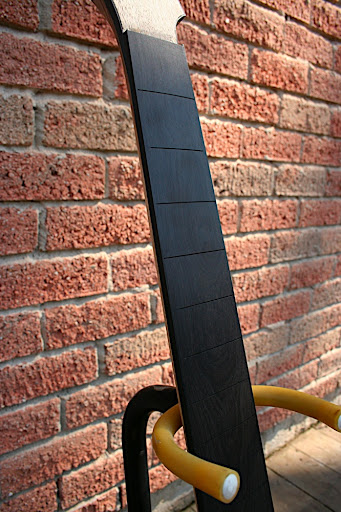 The ebony board has black binding on it, which ties it into the black binding around the rest of the guitar's top. The finished look will be super-clean.