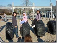 The girls pose on some giant tires on a bright sunny day