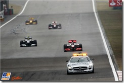The safety car leads the field. 