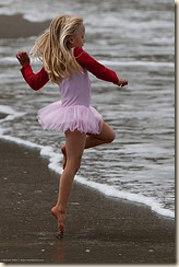 Cute Little Girl in Pink Dances on the Beach during the Kite Festival.