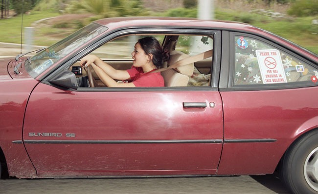 Woman meandering at differing speeds through various parts of Pacific Palisades, California, while singing, before noon on a weekend day in the early part of 1997