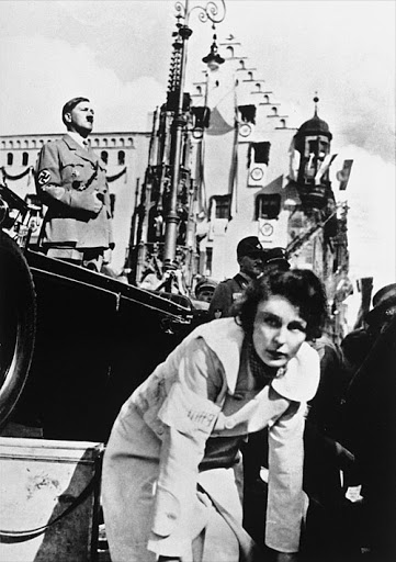 Leni Riefenstahl directing, with Adolf Hitler in the background