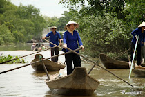 Women pushing their Vietnamese boats along on a creek in the Mekong delta