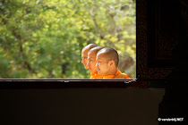 Three monks in a row outside a temple on the Royal Palace grounds, posing for a picture