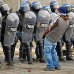 A protester urinates in front of a row of policemen during riots following the death of a 15-year-old boy in San Carlos de Bariloche June 18, 2010. According to local media, provincial government officials have confirmed that four police officers, involved in the incident which left the boy dead during an alleged robbery, have been removed from their posts. Three people have died and at least 12 have been injured during the clashes. Picture taken June 18, 2010. REUTERS/Alejandra Bartoliche (ARGENTINA - Tags: CIVIL UNREST CRIME LAW POLITICS IMAGES OF THE DAY)   FOR BEST QUALITY IMAGE: ALSO SEE GM1E6721UF901.F來㔓儴㕮ཿ㎬♴拫ሒ䪡睈ⴙ撺ᩪ