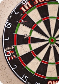 Close up of a dart board with arrow in the bullseye.