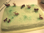 Plastic deer frolicking through the icing of a sheet cake.