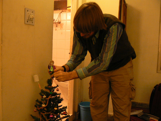 Nathaniel puts the foil angel on top of our mini Christmas tree.