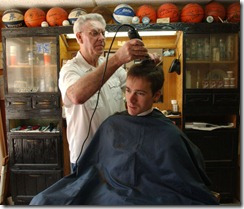 Jesse Joyner, an Asbury Seminary student gets his haircut, Friday, April 16, 2004, by Clay Tankersley, of Clay's Barbershop in downtown Wilmore. Tankersley has been cutting hair in the same location in since 1956.(Photo by Tim Webb, April 16, 2004)