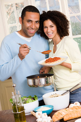 An African-American couple smiling and cooking in the kitchen.