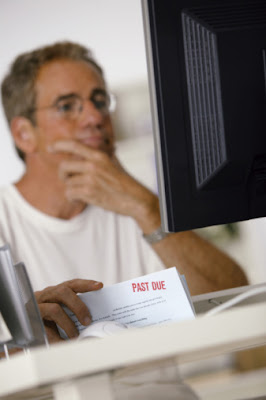 Man using a computer and holding up a past due bill.