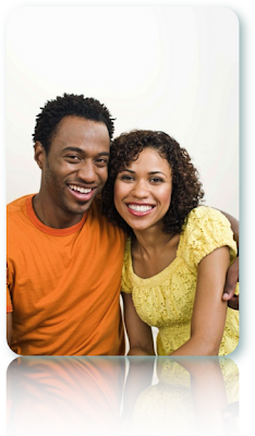 Black couple smiling, wearing bright clothing