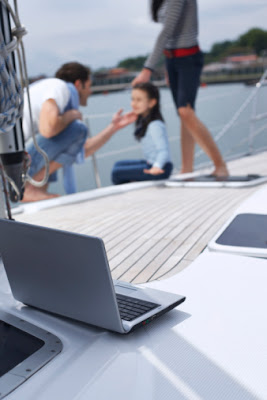 Laptop on a family sailboat used to request payday advance loans online.