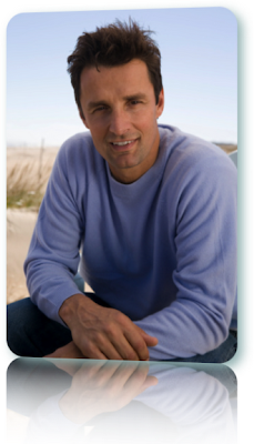 Man in a long-sleeved blue shirt smiling.