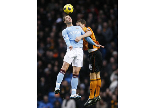Edin Dzeko jumps with Christophe Berra, Manchester City - Wolverhampton Wanderers