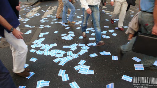 Feet Walking on Scattered Flyers in Buenos Aires, Argentina