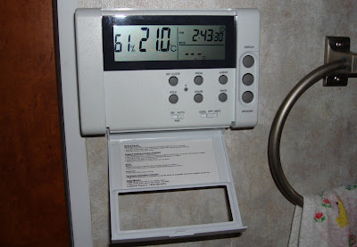 Digital programmable thermostat with front panel open.