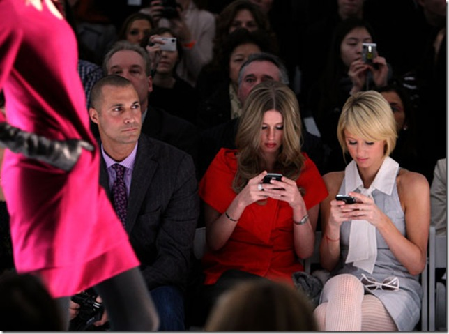 Nikki and Paris Hilton Text at Pamela Roland Fashion Show