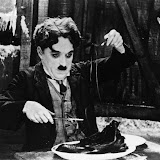 """01 Jan 1925 --- Charlie Chaplin eating a shoe in the classic scene from the """"The Gold Rush,"""" 1925.  Movie still. --- Image by © Bettmann/CORBIS"""