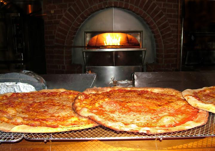 Duas pizzas em frente a um forno a lenha