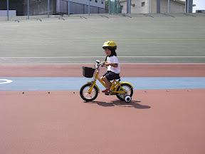 補助輪付きの幼児車に乗るお嬢ちゃん