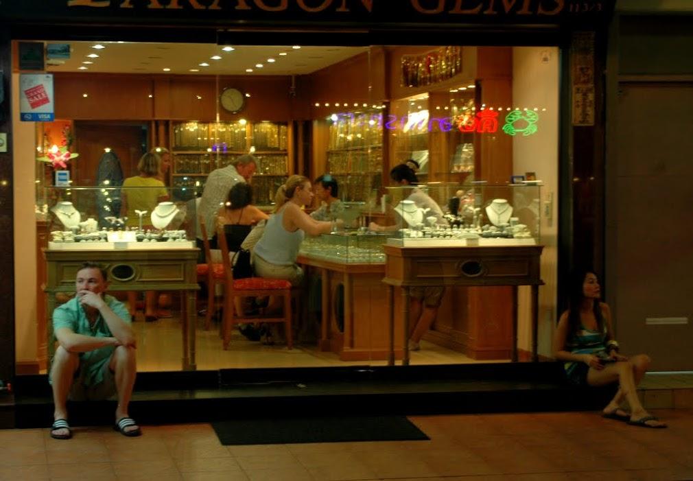 Мужчина ждет женщину, выбирающую украшения в ювелирном магазине