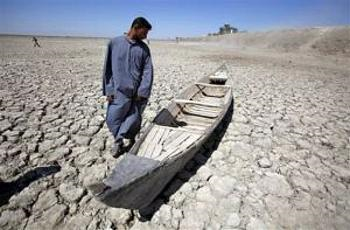 Akeed Abdullah stands next to his boat in a dried marsh in Hor al-Hammar in southern Iraq. (Photo by Gorillas Guides)