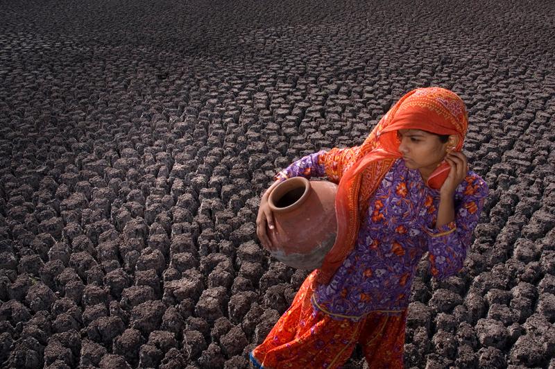 The picture depicts a young Indian girl dressed in a colorful blue and orange saree with pot in hand walking through the dry and cracked bed of Kal Bhairav Lake, where she once drew water. Now, she makes a daily journey to fetch water delivered by the National Defence's trucks, courtesy of the state government of Madhya Pradesh, India. 2009 photo contest: Chetan Soni