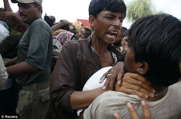 Desperate: Refugees fight to get food donated by a local charity in the village of Karamdad Qureshi in Punjab province, 22 August 2010. Some 20 million people have been affected by the worst flooding in Pakistan's history. Reuters