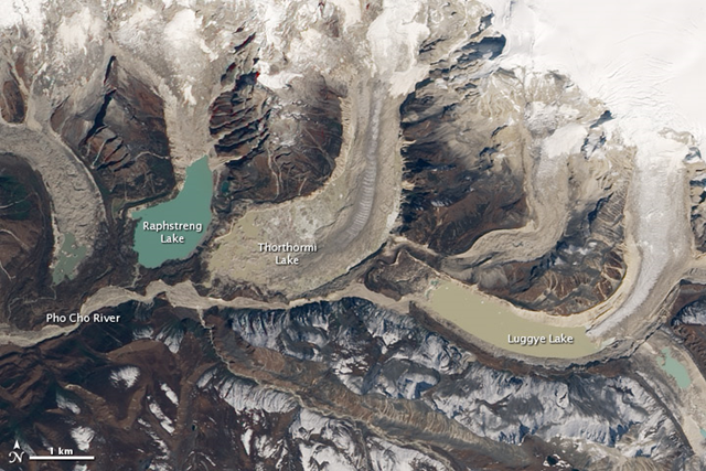 Thorthormi Glacier Lake, Bhutan Himalayas, acquired October 28, 2009. This natural-color image of the southern slopes of Bhutan's Table Mountain shows where the 1994 glacial outburst flood occurred. Luggye Lake broke through the moraine at the southwest corner, and the flood scoured a path down the Pho Cho River. NASA Earth Observatory image by Robert Simmon
