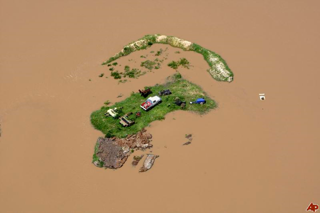 In this Tuesday, Jan. 4, 2011 photo, an island is formed by flood water stranding vehicles and other equipment in Rockhampton, Australia. Floods that have cut air, rail and road links to an Australian coastal city are now threatening its sewage plant, and waters are still expected to rise another few feet before peaking Wednesday. AP Photo / Janie Barrett, Pool