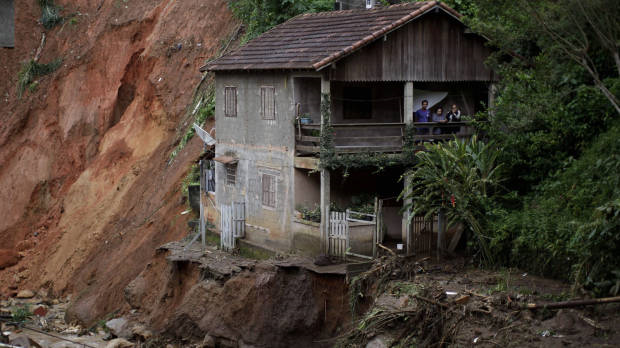 Residents stand on the porch of their home at the edge of landslide damage in the Caleme neighbourhood of Teresopolis, Brazil, 14 January 2011. Felipe Dana / AP