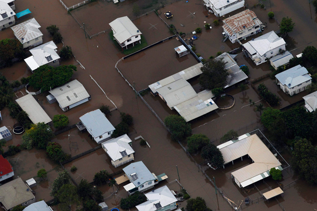 Buildings are submerged in floodwaters in a neighborhood in Rockhampton, Queensland on January 2, 2011. Large parts of Australia's coastal northeast were flooded on Sunday in a spreading environmental disaster as thousands of residents fled their homes to avoid the runoff from a Christmas deluge. REUTERS / Daniel Munoz