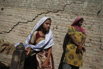 Gul Bahar, a nine-year-old flood survivor, stands with her mother in front of a damaged wall at their house in the village of Murad Chandio, some 35 km (22 miles) from Dadu in Pakistan's Sindh province, January 26, 2011. REUTERS / Akhtar Soomro