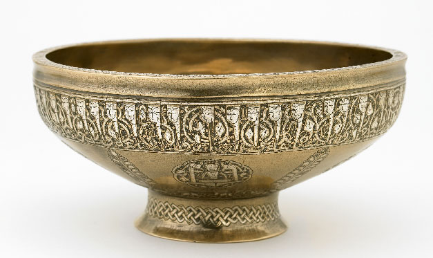 With the growing sophistication of inlay techniques in the thirteenth century, the art of calligraphy began to play a central role on metal objects. As this elegant stem bowl indicates, inscriptions often functioned as the principal means of embellishment. Most inscriptions consisted of blessings and short prayers addressed to anonymous patrons. The inscription on this bowl is particularly notable for its human-headed letters, a highly inventive style that developed in the thirteenth century and was used exclusively on metalwork intended for use in secular settings. Present-day Afghanistan, Herat. Early 13th century. 8.7 x 19.5 x 19.5 cm. Kufic script. Courtesy of the Freer Gallery of Art, Smithsonian Institution.