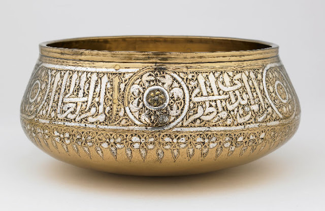 According to the elegant inscription encircling the rim of this fine beaten-brass bowl, it was made for the Mamluk sultan al-Malik al-Muzaffar, Saif al-Din Hajji, who ruled for only one year from 1347 to 1348. Like many other Mamluk vessels, the bowl's interior base is adorned with a fish-whirl design centered on a radiating sun disk. Egypt or Syria. 1346-1347 A.D. 10.3 x 23.5 x 23.5 cm. Courtesy of the Freer and Sackler Galleries, Smithsonian Institution; Lent by the Nuhad es-Said Collection.