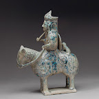 This figurine represents the relatively rare sculptural tradition within Islamic art. Although the function of this and other such Seljuq equestrian figures is not entirely known, they appear to portray significant personages. Here the overall symbolism conveyed is that of a warrior or hunter: the rider holds a cup, carries a short staff, and bears what appears to be a shield. The small animal seated behind the rider may be a hunting cheetah, and the hollowness of the object's upper section suggests a container-like function.