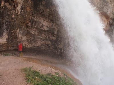 La Sílvia passant per darrere la cascada