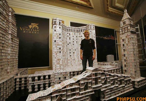Bryan Berg of the U.S. poses at his creation of the replica of The Venetian Macao-Resort-Hotel, as he breaks his own Guinness World Record for the largest house of Freestanding playing cards at The Venetian Macau Wednesday, March 10, 2010. Bryan used 218,792 playing cards to build a replica of The Venetian Macao-Resort-Hotel during the 44 day project. The final composition is 35 feet long, 10 feet tall and weight 272kg.  (AP Photo/Kin Cheung)