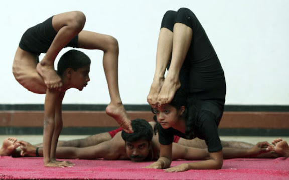 Indian students of a yoga college shows their skills during a function in Bangalore on May 19, 2010.  The function was organised to promote yoga and make people aware of helthy living through the regular practice of yoga.   AFP PHOTO/Dibyangshu SARKAR (Photo credit should read DIBYANGSHU SARKAR/AFP/Getty Images)