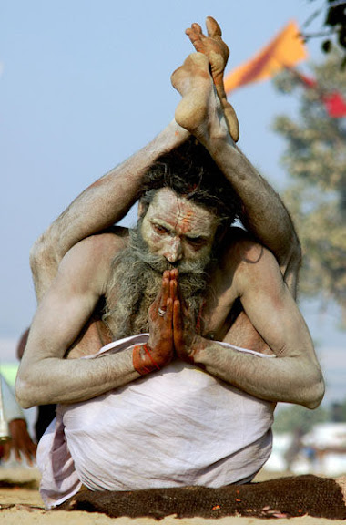 Allahabad, INDIA:  Indian Sadhu Yogiraj Srikant, performs yoga after taking a dip at Sangam, the confluence of the Ganges and Yamuna rivers, during the Ardh Kumbh Mela in Allahabad, 09 January 2007. Hundreds and thousands of devotees and Hindu holy men are taking part in the largest religious congregation of the world on the banks of Sangam, the confluence of the rivers Ganges, Yamuna and the mythical Saraswati, during the Ardh Kumb Mela (fair) which lasts 45 days and commemorates a mythical battle between gods and demons over a pitcher of the nectar of immortality. AFP PHOTO/STR  (Photo credit should read STRDEL/AFP/Getty Images)