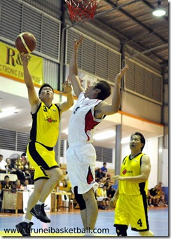 Lim Thin Teck (L) of the veteran national basketball team going for a layup against Huong Yu Hua (R) of Miri during their match for the 11th Borneo City Veteran Basketball Invitation Tournament 2010 last night.Picture: BT