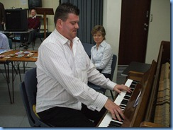 Chris Larking playing the piano whilst fellow pianist Denise Gunson watches on with interest