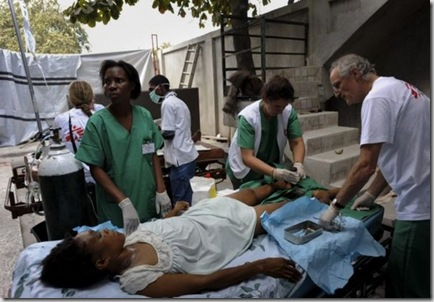 A #Haitian doctor, UK surgeon, and German nurse treat a patient with two broken legs. © Julie Remy