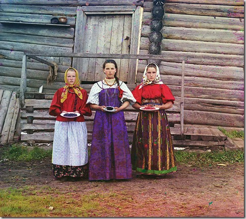 Peasant girls, Russian Empire. Three young women offer berries to visitors to their izba, a traditional wooden house, in a rural area along the Sheksna River, near the town of Kirillov; 1909 Sergei Mikhailovich Prokudin-Gorskii Collection (Library of Congress).