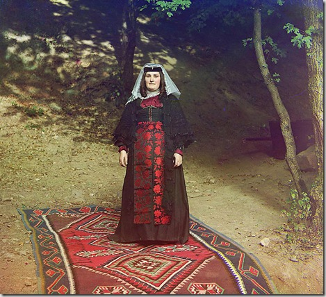 Georgian woman standing on a carpet, outside, near a tree; between 1905 and 1915 Sergei Mikhailovich Prokudin-Gorskii Collection (Library of Congress).