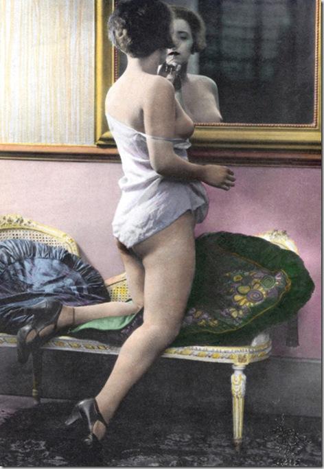 EROS giovane donna  in sottoveste davanti allo specchio, si ritocca il trucco; fa pensare che si prepari a esercitare la sua professione di seduttrice, in una casa chiusa. Fotografia, primi anni del XX secolo