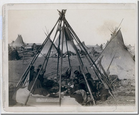 "Title: ""Home of Mrs. American Horse."" Visiting squaws at Mrs. A's home in hostile camp Oglala women and children seated inside an uncovered tipi frame in an encampment--most are looking away from the camera--probably on or near Pine Ridge Reservation. 1891. Repository: Library of Congress Prints and Photographs Division Washington, D.C. 20540"