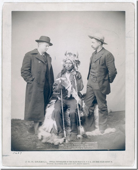 "Title: ""Little,"" the instigator of Indian Revolt at Pine Ridge Little, Oglala band leader, full-length studio portrait seated between two Euro-American men who are standing on either side of him; Chris Mathison (?) on left. 1890. Repository: Library of Congress Prints and Photographs Division Washington, D.C. 20540"