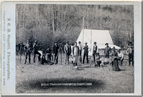 Title: [Engineers Corps camp and visitors] Row of fifteen people and two deer in front of a tent. Some of the men are holding measuring poles and or standing next to surveyors' transits on tripods. 1889. Repository: Library of Congress Prints and Photographs Division Washington, D.C. 20540